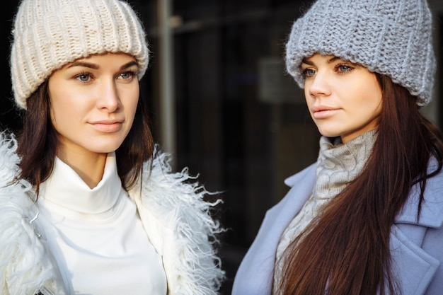 Chiuda su un ritratto di due giovani donne degli amici bei in autunno Foto Premium