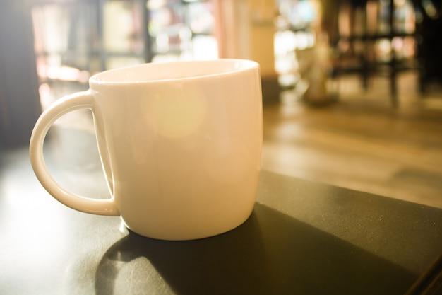 Chiuda su una tazza di caffè bianca sull'effetto nero del filtro dal chiarore del sole della tavola Foto Premium