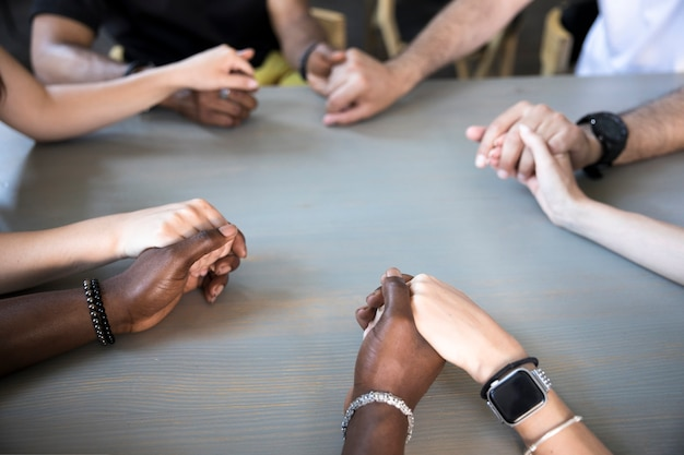Chiuda sugli amici interrazziali che pregano Foto Gratuite