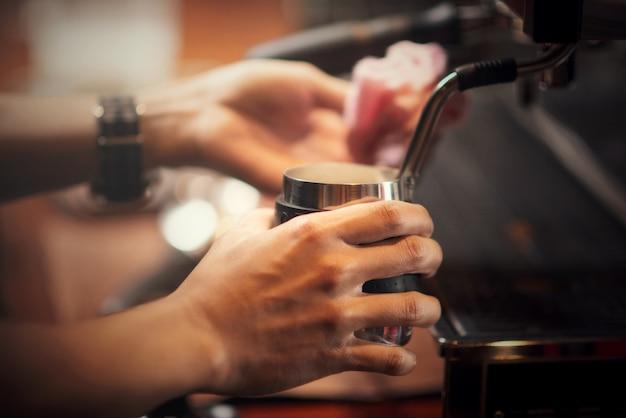 Chiuda sul barista che produce il cappuccino, barista che prepara la bevanda del caffè Foto Gratuite