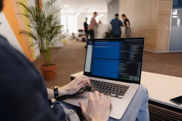 Chiuda sul codice di scrittura dell'uomo sul computer portatile Foto Gratuite