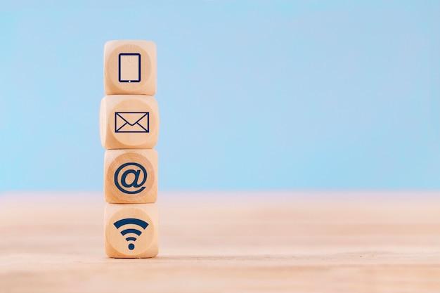 Chiuda sul cubo del blocco di legno con il telefono cellulare, l'e-mail, l'indirizzo e il wifi dell'icona di comunicazione sulla tavola Foto Premium