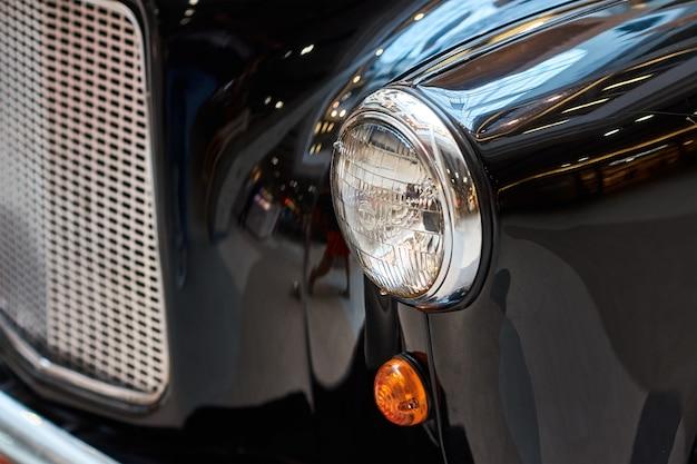Chiuda sul faro di un'automobile nera dell'annata Foto Premium