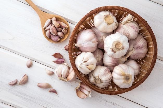 Chiuda sul gruppo di aglio su un piano di appoggio di legno bianco Foto Premium
