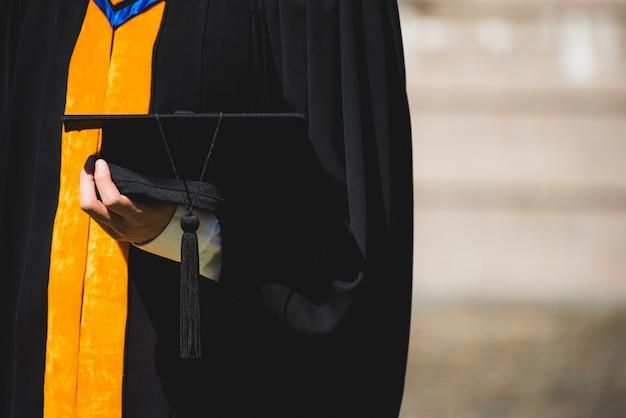 Chiuda sul laureato che tiene un cappello. il concetto ha successo nell'università Foto Premium