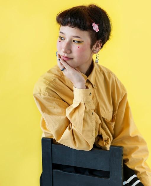 Chiuda sul modello che si siede sulla sedia Foto Gratuite