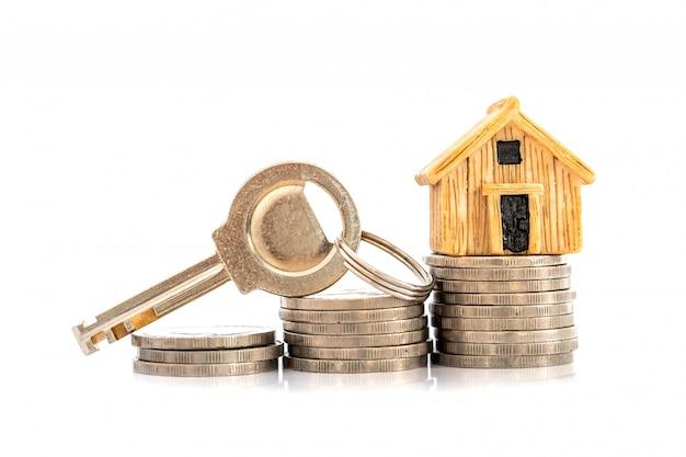 Chiuda sul posto del modello della casa sull'accatastamento della moneta dei soldi per un'ipoteca domestica e un prestito, un rifinanziamento o un investimento immobiliare Foto Premium