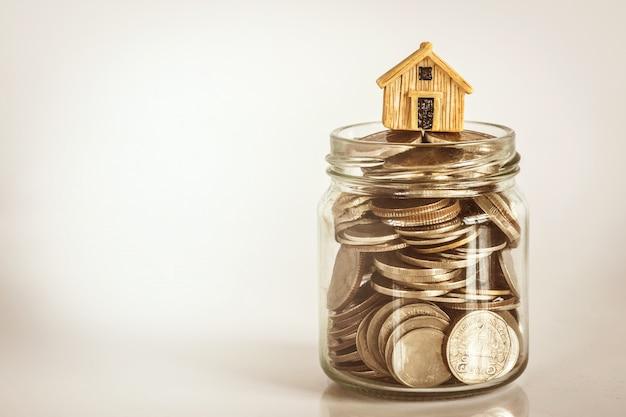 Chiuda sul posto di modello della casa sull'impilamento della moneta dei soldi per un'ipoteca e un prestito domestici Foto Premium