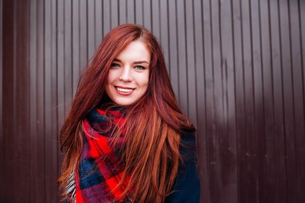 Chiuda sul punto di vista della donna caucasica felice attraente con i capelli dello zenzero che indossano i vestiti alla moda che guardano e che sorridono Foto Premium
