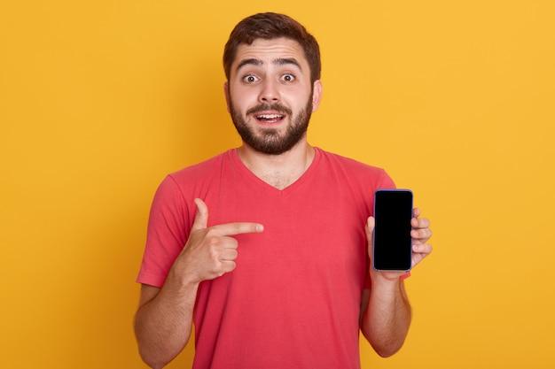 Chiuda sul ritratto del giovane bello sicuro che mostra il suo telefono e che indica con il dito indice sullo schermo del dispositivo Foto Gratuite