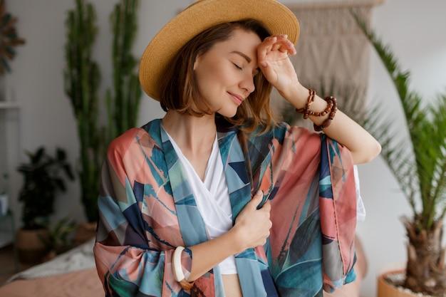 Chiuda sul ritratto della donna elegante in cappello di paglia che posa nella sua camera da letto nello stile di boho Foto Gratuite