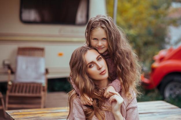 Chiuda sul ritratto della madre e della piccola figlia che abbracciano e che si rilassano nella campagna sulla vacanza del camper Foto Premium