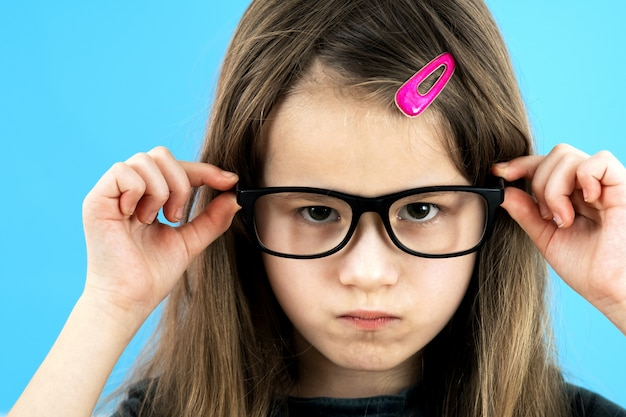 Chiuda sul ritratto della ragazza arrabbiata dispiaciuta arrabbiata della scuola del bambino che indossa i vetri di sguardo isolati su fondo blu. Foto Premium
