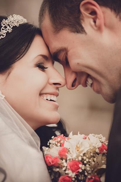 Chiuda sul ritratto della sposa e dello sposo felici Foto Premium