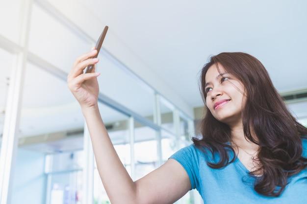 Chiuda sul ritratto delle donne asiatiche che indossano le camice blu stanno stando a prendere i selfies Foto Premium
