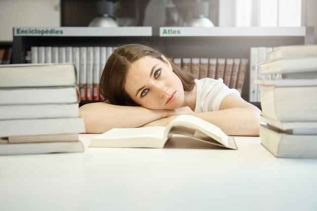 Chiuda sul ritratto di giovane studente alla biblioteca che prepara per gli ultimi esami, appoggiando la testa sulle mani, sembrando triste e stanco Foto Gratuite