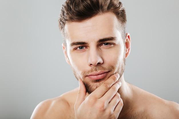 Chiuda sul ritratto di un giovane uomo barbuto che guarda l'obbiettivo Foto Gratuite