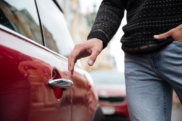 Chiuda sul ritratto di una mano maschio alla maniglia dell'automobile all'aperto Foto Gratuite