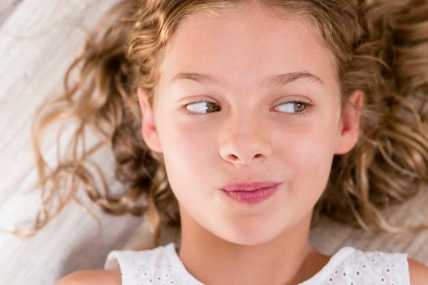 Chiuda sul ritratto di una ragazza giovane e bella del bambino che pensa e che distoglie lo sguardo con l'espressione divertente. occhi verdi, capelli biondi. ambientazione interna. vista dall'alto Foto Premium