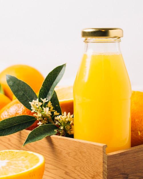 Chiuda sul succo d'arancia in una bottiglia Foto Gratuite