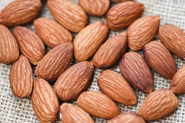 Chiuda sull'alimento della proteina naturale delle noci della mandorla e per lo spuntino - mandorle sul fondo del sacco Foto Premium