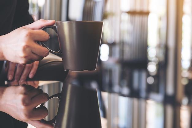 Chiuda sull'immagine di una donna che tiene le tazze da caffè con la riflessione Foto Premium