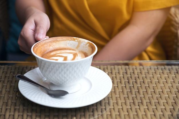 Chiuda sull'immagine di una donna che tiene le tazze di un caffè macchiato in caffè Foto Premium