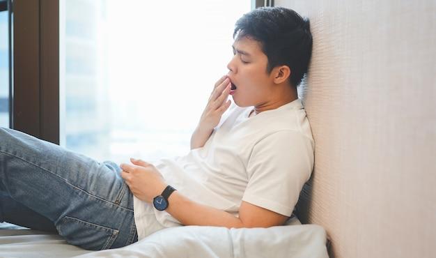 Chiuda sull'uomo asiatico assonnato e che sbadiglia alla camera da letto nel giorno di vacanza Foto Premium