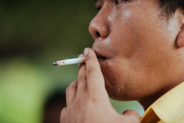 Chiuda sull'uomo che fuma una sigaretta Foto Gratuite
