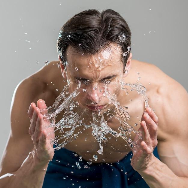 Chiuda sull'uomo che lava il suo fronte con acqua Foto Gratuite