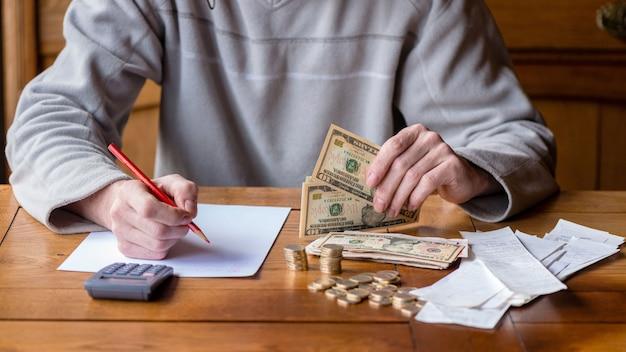 Chiuda sull'uomo con il conteggio del calcolatore, prendendo le note a casa, la mano è scrive in un taccuino. monete impilate sistemate a deesk. concetto di finanze di risparmio. Foto Premium