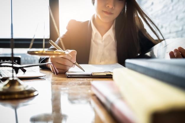 Chiuda sull'uomo d'affari dell'avvocato che lavora o che legge il libro di legge nel posto di lavoro dell'ufficio per il concetto dell'avvocato del consulente. Foto Premium