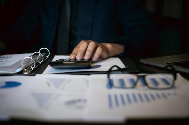 Chiuda sull'uomo d'affari facendo uso del calcolatore e del computer portatile per fanno le finanze di per la matematica sullo scrittorio di legno Foto Premium