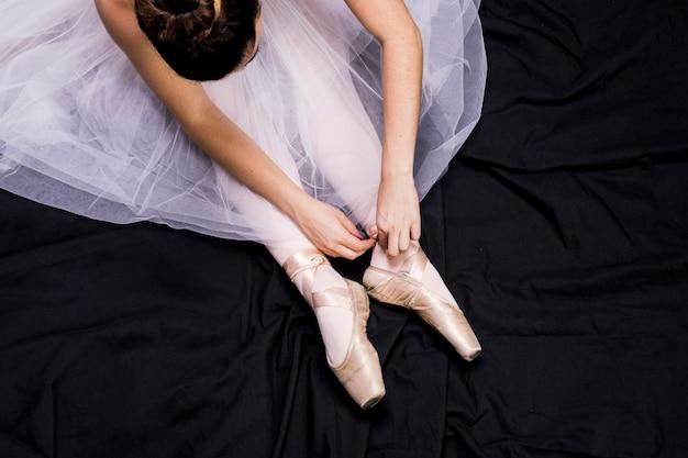 Chiuda sulla ballerina che lega le sue scarpe da punta Foto Gratuite