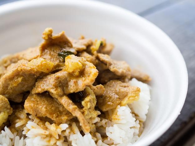 Chiuda sulla carne di maiale rossa del curry con riso in tazza della schiuma Foto Premium
