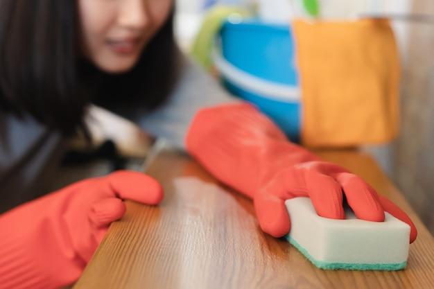 Chiuda sulla cucina di pulizia della donna facendo uso dello spruzzo e del panno della pulitrice. Foto Premium