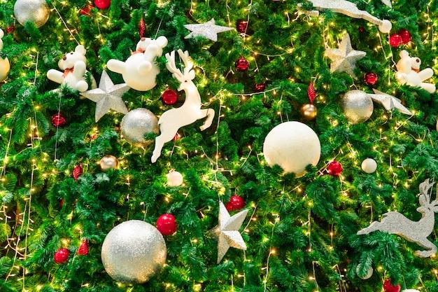 Chiuda sulla decorazione dell'albero di natale con le palle, la stella d'argento e la renna bianca. sfondo di natale. Foto Premium