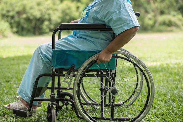 Chiuda sulla donna anziana sola che si siede sulla sedia a rotelle al giardino in ospedale Foto Gratuite