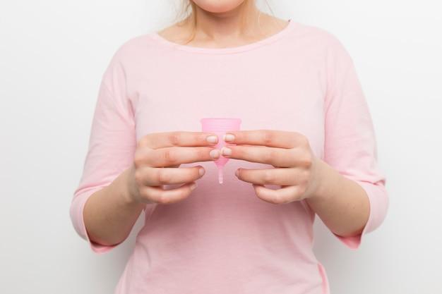 Chiuda sulla donna che tiene la tazza mestruale Foto Gratuite