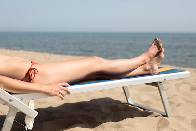 Chiuda sulla donna di vista laterale sulla sedia di spiaggia che prende il sole Foto Gratuite