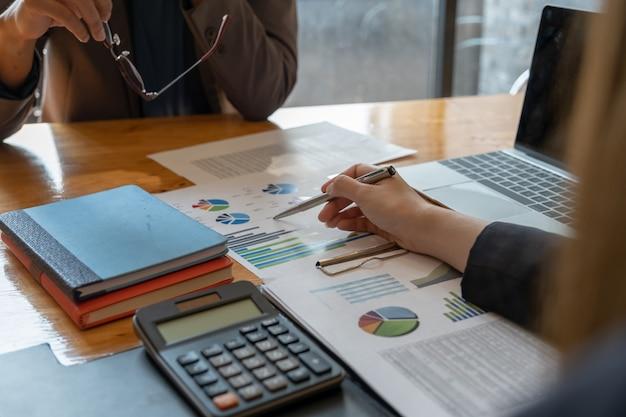 Chiuda sulla donna e sul partner di affari discutono sul programma del bilancio, sulla tassa, sulla contabilità, sulle statistiche Foto Premium