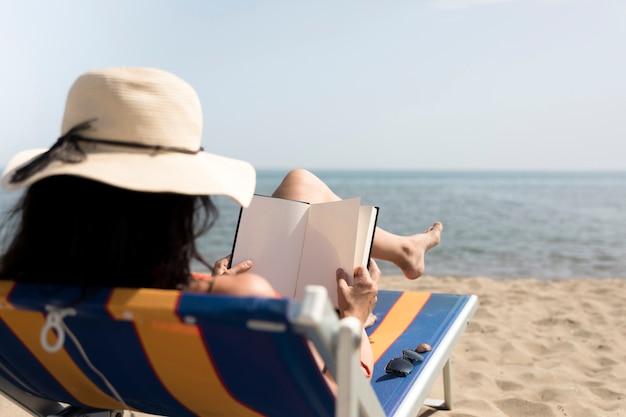 Chiuda sulla donna posteriore di vista su lettura della sedia di spiaggia Foto Gratuite
