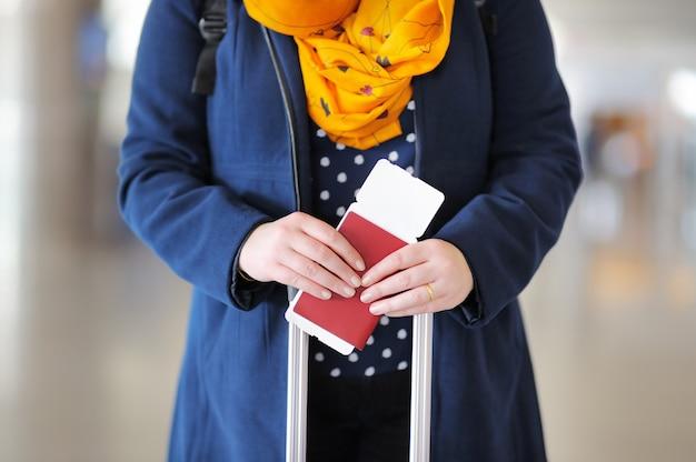 Chiuda sulla foto del passaporto della tenuta della donna e della carta d'imbarco all'aeroporto Foto Premium