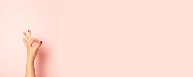 Chiuda sulla foto della mano della giovane donna che mostra il gesto giusto isolato sul rosa Foto Premium