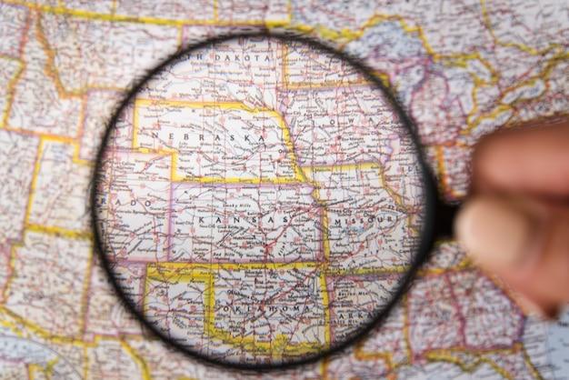 Chiuda sulla lente d'ingrandimento che mostra i posti sulla mappa Foto Gratuite