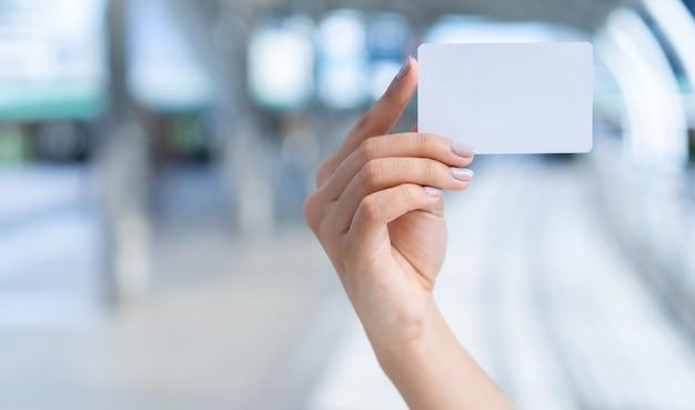 Chiuda sulla mano caucasica della donna che tiene il biglietto da visita bianco in bianco sul fondo vago del percorso del corridoio per, mostri, promuova il contenuto e il messaggio Foto Premium