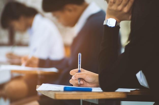 Chiuda sulla mano dell'esame di lettura e di scrittura dello studente con lo sforzo in aula Foto Premium