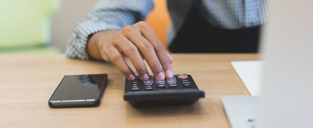 Chiuda sulla mano dell'uomo del proprietario di affari facendo uso del calcolatore per lavorare all'ufficio Foto Premium