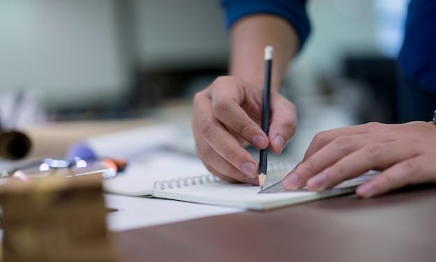 Chiuda sulla mano dell'uomo dell'architetto facendo uso della progettazione di piano del disegno a matita dei lavori di costruzione sul libro di schizzo Foto Premium