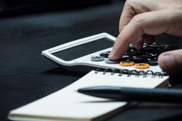 Chiuda sulla mano dell'uomo facendo uso del calcolatore sul fondo di legno dello scrittorio. Foto Premium